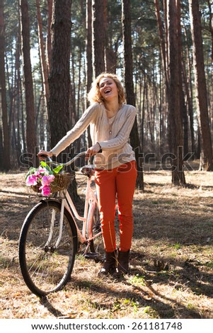 Beautiful young laughing woman on retro bike with tulips in basket in sunny park