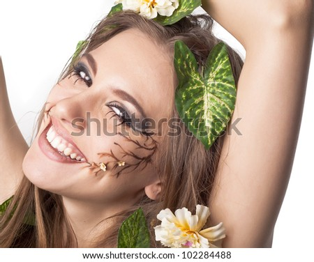 Beautiful young laughting woman with flowers, leaves in her hair and original make up - stock photo