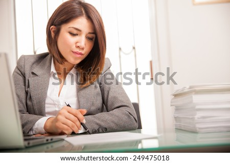 Beautiful young lawyer reviewing and signing a lot of documents at work - stock photo