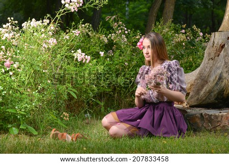 Beautiful young laying on field of grass and playing with flowers