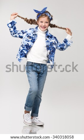 Beautiful young little girl standing posing in the studio on a white background wearing blue denim jeans, white shirt, colorful vest, plays, funny time. - stock photo