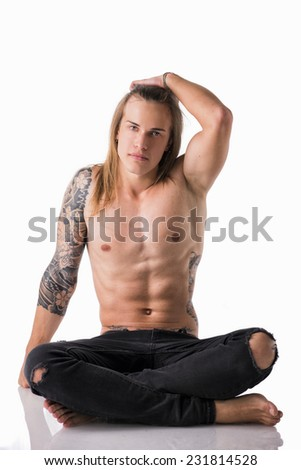 Beautiful young long haired man shirtless, sitting on the floor looking at camera - stock photo