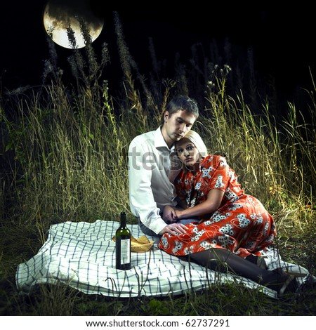 Beautiful young lovers in the moonlight picnic - stock photo