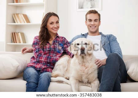 Beautiful young loving couple is sitting on sofa and embracing. They are stroking the dog and smiling. The man and woman are looking at camera happily - stock photo