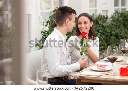Beautiful young man and woman are celebrating Valentine day at restaurant. They are sitting at the table and smiling. The man is giving a rose to his girlfriend - stock photo