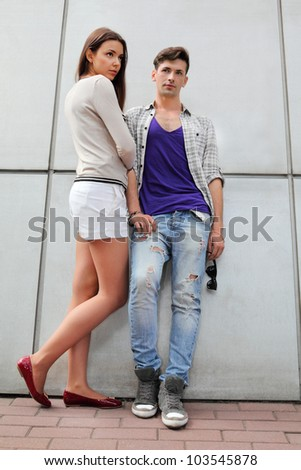 Beautiful young man and woman stand near gray wall and look not at camera - stock photo