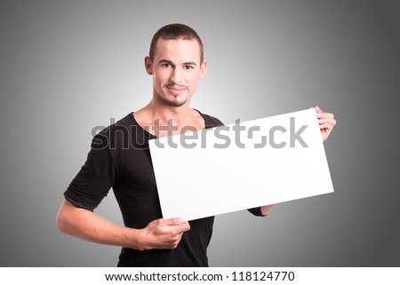 Beautiful young man holding a white cupboard - stock photo
