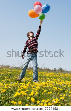 beautiful young man in a spring field with lots of balloons - stock photo