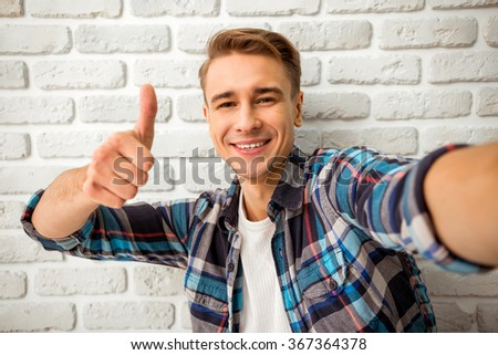 Beautiful young man in casual clothes make selfie on a background of white brick wall - stock photo