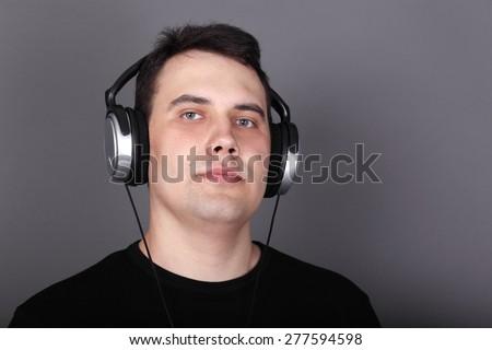 Beautiful young man in headphones and black t-shirt in grey studio - stock photo