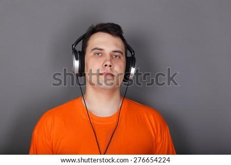 Beautiful young man in headphones and orange t-shirt in grey studio - stock photo