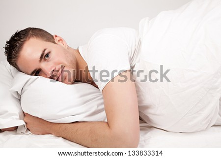 beautiful young man lying in bed - stock photo
