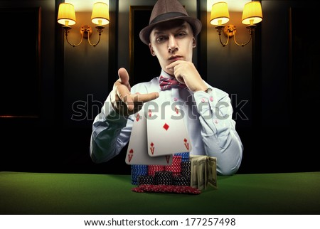 Beautiful young man on a beautiful background playing poker. Good luck in card games on the big money. - stock photo
