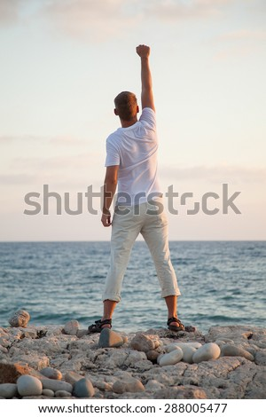 Beautiful young man on the seashore at daybreak