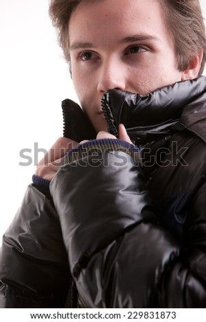 beautiful young man posing in winter with a warm anorak