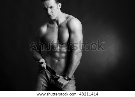 Beautiful young man posing on dark background - stock photo