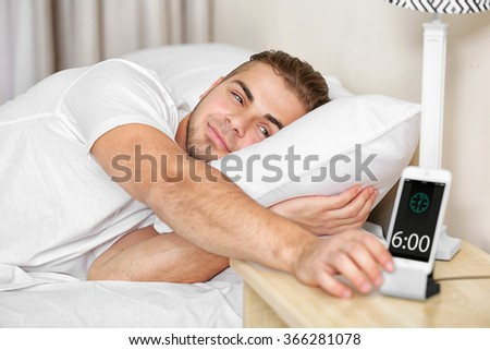 Beautiful young man waking up with mobile alarm clock - stock photo