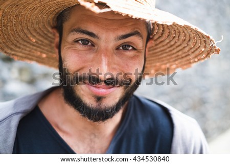 Beautiful young man with a straw hat - stock photo