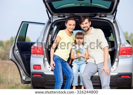 Beautiful young married couple and their daughter are sitting on boot of car outside. They are embracing and smiling. They are looking at camera happily. The small girl is holding flowers - stock photo