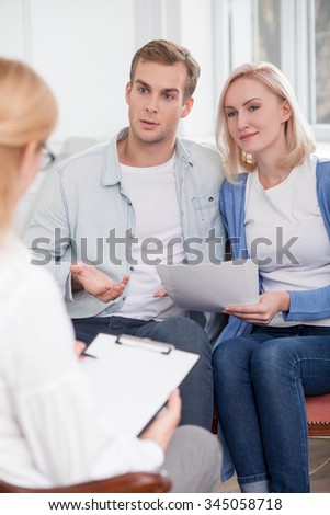 Beautiful young married couple is visiting a female psychologist. They are sitting and holding papers. The couple is talking with a woman with interest and smiling - stock photo