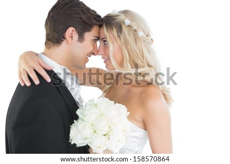 Beautiful young married couple looking each other in the face on white background - stock photo