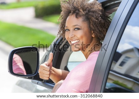 Beautiful young mixed race black African American woman giving thumbs up and driving a car - stock photo