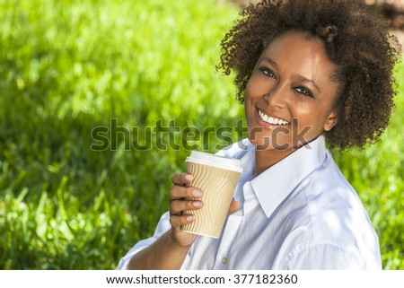 Beautiful young mixed race black African American woman smiling and drinking a takeaway cup of coffee outside - stock photo