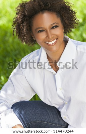 Beautiful young mixed race black African American woman with perfect teeth smiling and relaxing outside in summer sunshine - stock photo