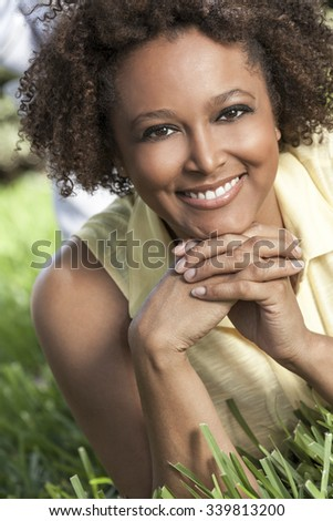 Beautiful young mixed race black African American woman with perfect teeth smiling and relaxing laying down on grass outside in summer sunshine