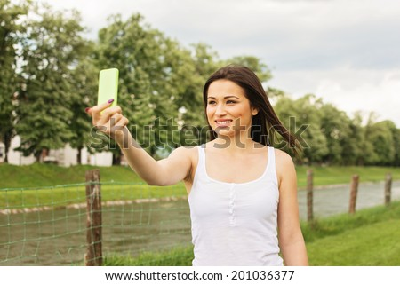 Beautiful young mixed race brunette woman taking a selfie with smart phone outdoors in summer in park. Horizontal image.