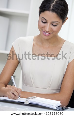 Beautiful young mixed race, Latina Hispanic woman or businesswoman in smart business suit sitting at a desk in an office writing in her diary - stock photo