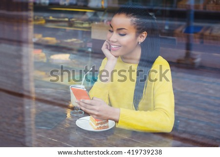 Beautiful young mixed race woman sitting in a coffee shop with her latte drink and a piece of cake, seen through the window while using her mobile phone - stock photo