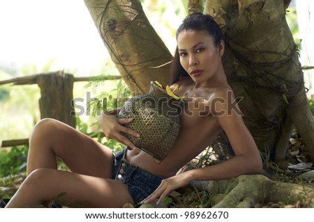 Beautiful young model from Thailand without blouse holding authentic wicker fishing basket filled with colorful flowers sitting in front of tree on sunny day. - stock photo