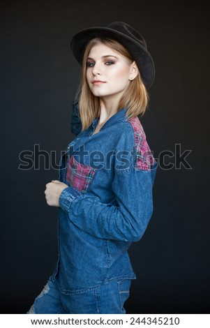 beautiful young model in a denim shirt and hat on a dark background