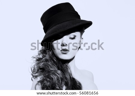 Beautiful young model in hat on the white background. Contrast photo - stock photo