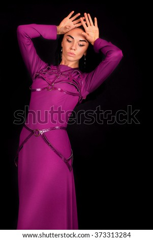 Beautiful young model in purple dress posing over black background. Fashion woman, beautiful woman, business girl, fashion girl, beautiful girl, fashion, style. - stock photo