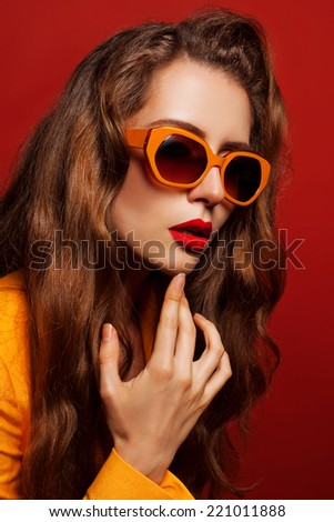 Beautiful young model in the orange jacket and sunglasses posing on red background