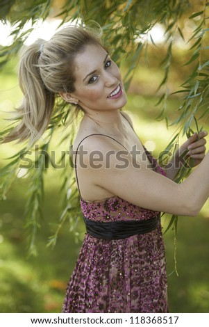 Beautiful young model standing in lush green meadow on sunny day.