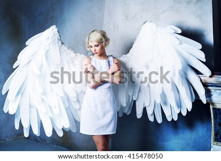 beautiful young model wearing a white dress with angel wings in the studio - stock photo