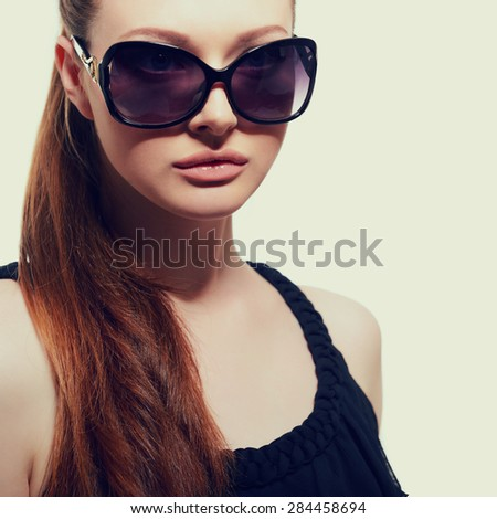 Beautiful young model with big sunglasses, close up, image toned.