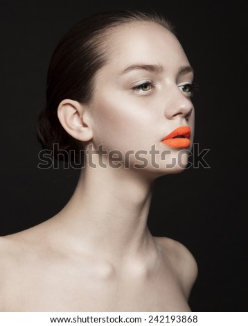 Beautiful young model with orange lips, healthy skin