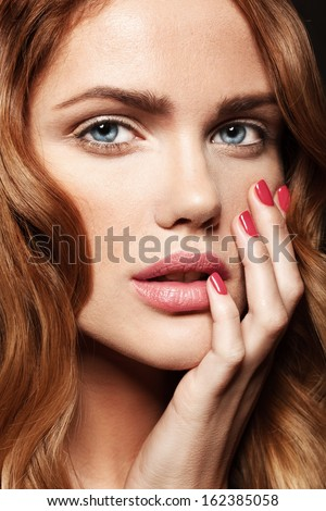 Beautiful young model with pink lips and colorful manicure - stock photo