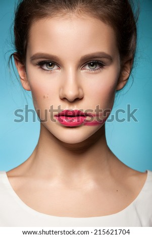 beautiful young model with pink lipstick smeared on her cheek, healthy skin on a blue background. Fresh Trendy summer makeup - stock photo