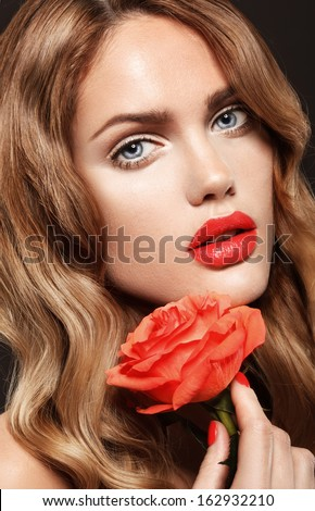 Beautiful young model with red lips and red manicure  Flower - stock photo