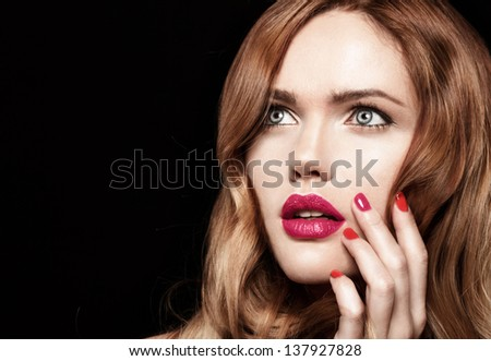 Beautiful young model with red lips and red manicure shine hair on black background