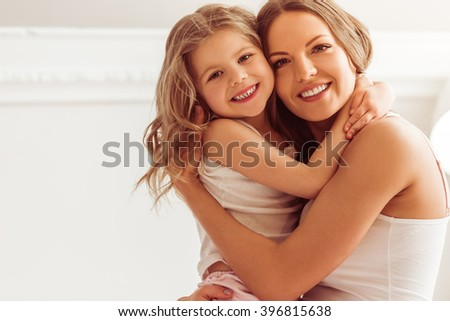 Beautiful young mom and her little daughter are cuddling, looking at camera and smiling while sitting on bed at home - stock photo