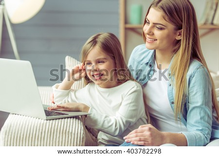 Beautiful young mom and her little daughter are using a laptop and smiling while sitting on sofa at home - stock photo