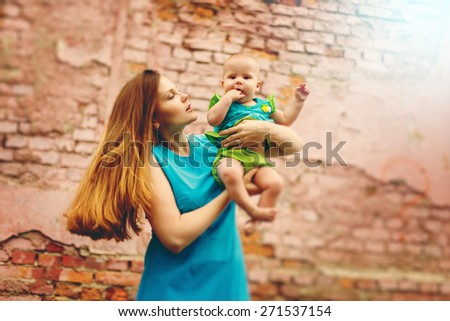 Beautiful Young Mom playing with her Cute Toddler Kid against Brick Wall. Image toned with Warm Colors. Selective focus, Shallow DOF. Grain added for best impression. - stock photo