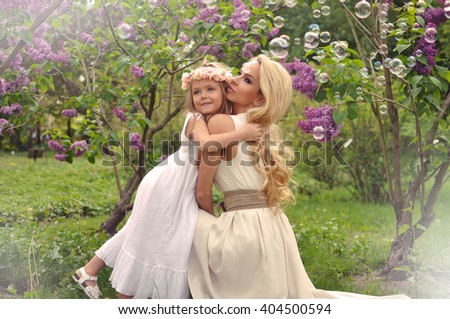 Beautiful Young MOM WITH A CHILD daughter are sitting on swing in the park GARDEN WITH FLOWERS In the lovely, ethereal communion dresses and joyfully to each other smile in SPRING SUMMER DAY - stock photo