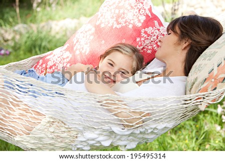 Beautiful young mother and daughter laying down and relaxing together on a hammock during a sunny summer day on holiday home garden. Family relaxing outdoors, healthy and wellness lifestyle. - stock photo